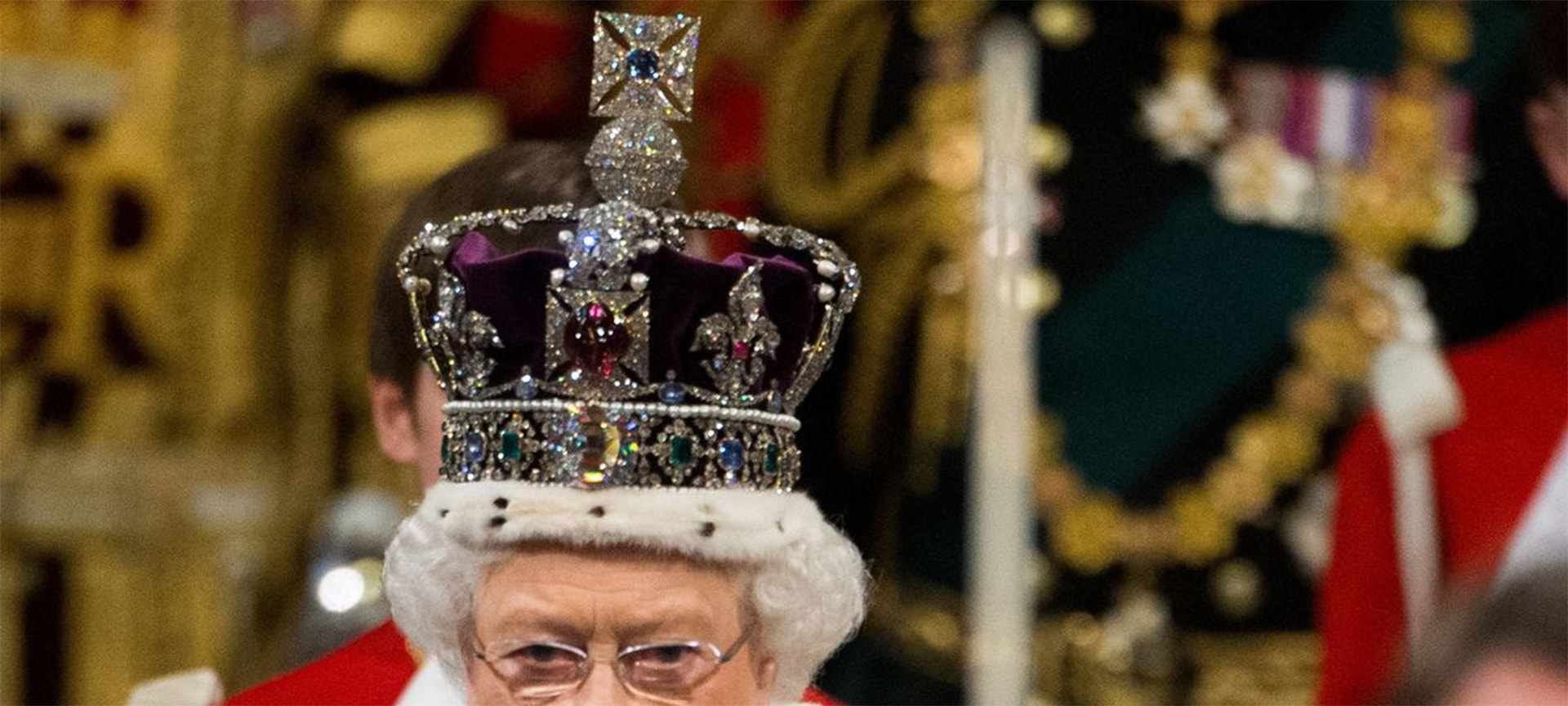 Queen Elizabeth II walks through the Royal Gallery during the State Opening of Parliament wearing a crown which carries one of the Cullinan diamonds.
